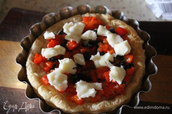 Вынимаем тарталетки из духовки, кладем начинку из перца, маслин и зелени. Сыр руками рвем на кусочки и раскладываем сверху.