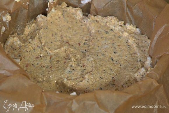 Разъемную форму выстелить бумагой для выпечки и равномерно выложить тесто.