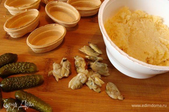 Сыр (типа гауды) натереть на мелкой терке. Смешать с соусом. У меня был горчичный соус, можно использовать любой по вкусу. Наполнить сыром тарталетки. Украсить огурчиком и ракушками.
