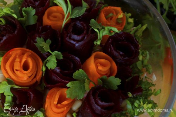 Теперь примемся за украшение. Для этого отварную свеклу и морковь очищаем от шкурки и при помощи очень тонкого ножа счищаем мякоть тоненькой лентой. Из этой ленты мы и будем скручивать цветы. Готовые цветы высаживаем на салат украшаем веточками петрушки, свободные места посыпаем мелконарезанным зеленым луком.
