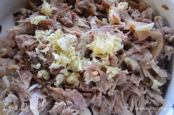 Мясо разобрать на волокна и добавить чеснок через пресс и свежемолотый черный перец, перемешать.