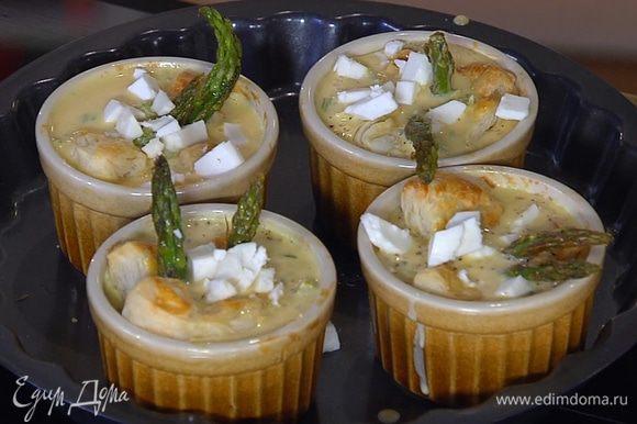 В подпеченное тесто воткнуть кусочки спаржи, залить сливочно-яичной начинкой и посыпать нарезанным козьим сыром.