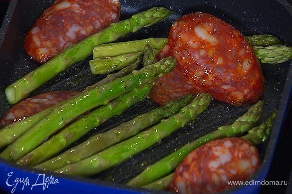 Когда спаржа будет практически готова, добавить в сковороду ломтики колбасы и обжаривать все еще пару минут.