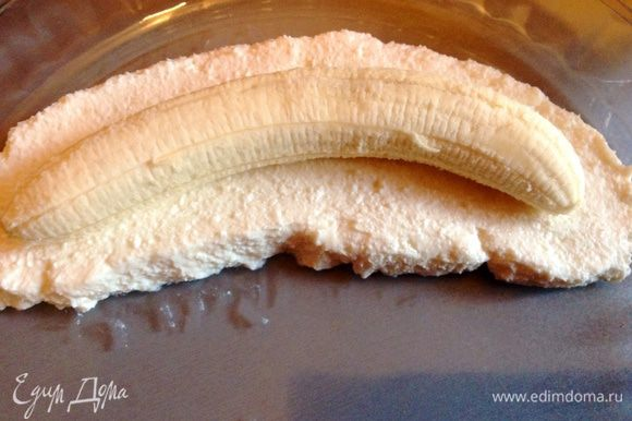 В творог добавить сметану и сахар, ванильный порошок, апельсиновую цедру и хорошо все перемешать, выложить подушку из смеси по форме банана как на фото, сверху положить очищенный целый банан.