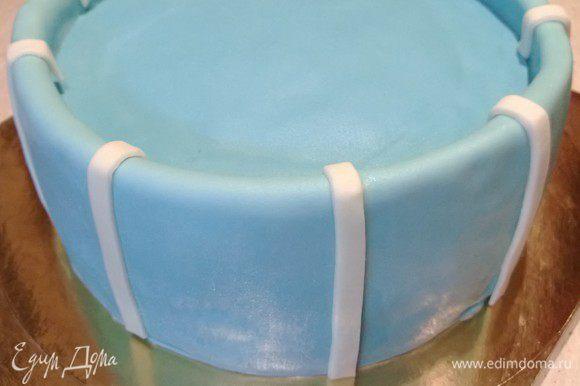 Покрыть торт голубой мастикой. Вырезать и добавить белые полосы из мастики по периметру.