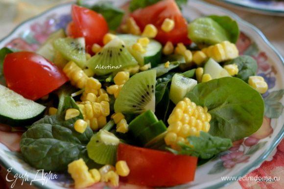 Разложим по тарелкам молодой помытый шпинат, либо можно заменить на салатный микс, такой как смесь руколы, шпината, молодых листьев салата. Помидор крупный разрезаем на несколько частей, кукурузу свежую очищаем от початка и срезаем острым ножом аккуратно желтые зерна, базилик листья свежие раскладываем по тарелкам, огурец тонко нарезаем, лук красный, киви или манго очищаем и на кубики.