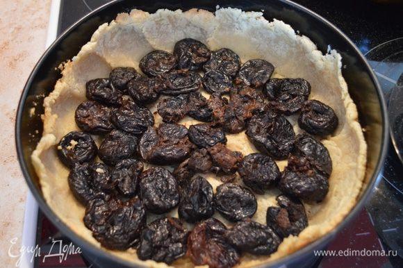 На слегка запеченное тесто выкладываем по кругу чернослив.