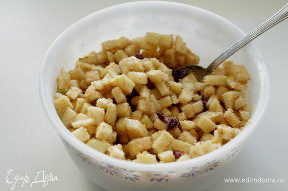 Яблоки очистите от кожуры и семечек, нарежьте кубиками, смешайте их с клюквой, сахаром, корицей и панировочными сухарями.