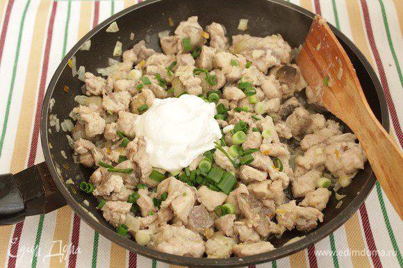 Добавьте рыбу и быстро обжарьте, аккуратно перемешивая, 3-5 мин. Мелко нарежьте зеленый лук и добавьте его к рыбе вместе со сметаной, немного потушите. Остудите до комнатной температуры.
