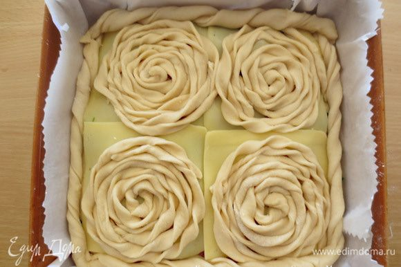 Из оставшегося теста раскатать более тонкий пласт, нарезать полоски 1-2 см шириной и 40 см доиной и закрутить спиральки, укладывая их на каждый пласт сыра. Для ободка пирога, используем спираль из полосок шириной 3 см Это нужно для того, чтобы края пирога получились закрытыми, так как их не залепляем. Яичный желток взбиваем и смазываем пирог. Оставляем на 10 минут и затем выпекаем при температуре 200 градусов примерно 40 минут. Время выпечки регулируйте в зависимости от Вашей духовки.