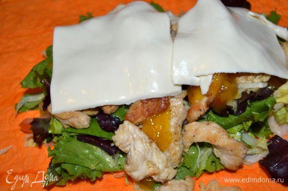 Затем выкладываем обжаренное филе, добавляем соус по вкусу (у меня кисло-сладкий с ананасом и имбирем, он отлично подошел по вкусу). Закрываем пластинками сыра.