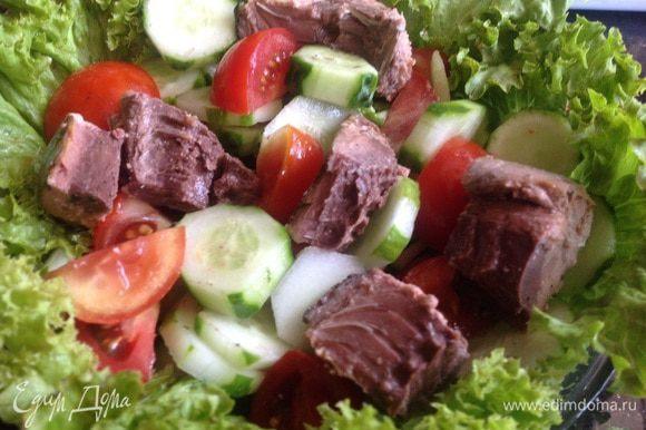 Слейте жидкость с тунца и выложите кусочки на салат. Сверху выложите маслины.