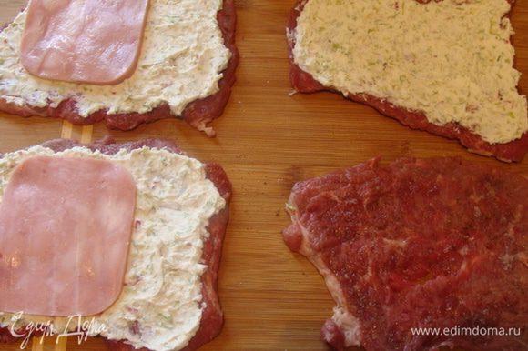 Мясо отбить, поперчить и посолить. Намазать на каждую отбивную творожную начинку и положить кусочек ветчины.
