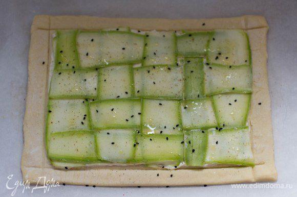 Цукини (или кабачок) нарезать тонкими пластиками. Выложить на начинку в виде плетенки. Сбрызнуть оливковым маслом, посыпать черным тмином