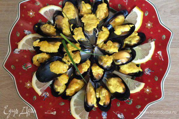 Добавляем в раковинки с мидиями шафрановый соус. Режем также лимон и зеленый лук по своему вкусу.