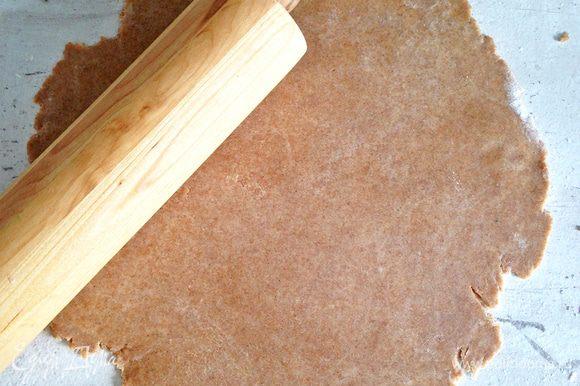 На слегка присыпанной мукой поверхности раскатываем тесто в круг, затем перекладываем его на коврик для выпечки или на пергамент.