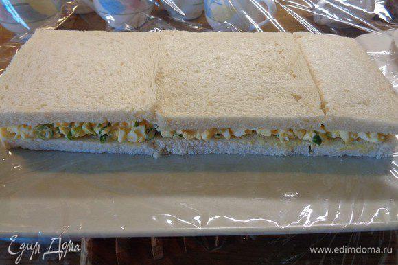Сверху уложить второй слой хлеба. Немного придавать рукой.