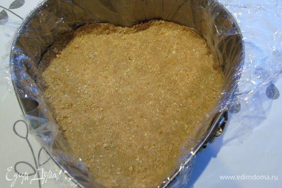 Форму застелить пленкой, так будет легче извлечь чизкейк, и выложить печенье, перемешанное с растопленным маслом. Хорошо утрамбовать. Уберите в холодильник.