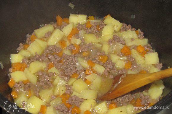Положить нарезанный небольшими кусочками картофель, все залить горячей водой, так, чтобы покрыть мясо и овощи. Посолить и поперчить по вкусу. Тушить 15 минут.