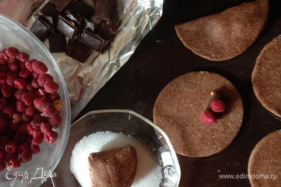 Затем визуально делим круг на 4 сектора и в правый нижний кладем начинку из дольки шоколада (у меня темный с дробленым лесным орехом) и пары ягод малины. Складываем пополам, а затем еще раз пополам (думаю, техника знакомая каждому дому). В миску насыпаем сахар и обмакиваем печенье стороной, где больше слоев теста. Хорошенько припечатываем, чтобы сахара хватило, так как в тесте его немного, и выкладываем на противень, застеленный пергаментом или фольгой.