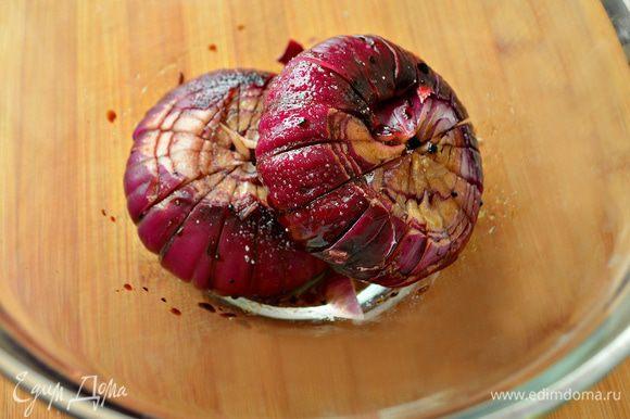 Красный лук очистить, сделать надрезы, но не до конца, разделив луковицы на 8-10 равных частей. Положить луковицы в миску и залить оливковым маслом с бальзамическим уксусом. Затем хорошенько обвалять лук в этом соусе, посолить, поперчить и выложить на противень, полив соусом из масла и бальзамического уксуса. Накрыть противень фольгой и запекать луковицы 20 минут при температуре 200 градусов, а затем еще 10 минут без фольги. Одну запечённую луковицу разобрать на дольки и добавить в салат, вторую - оставить для украшения.