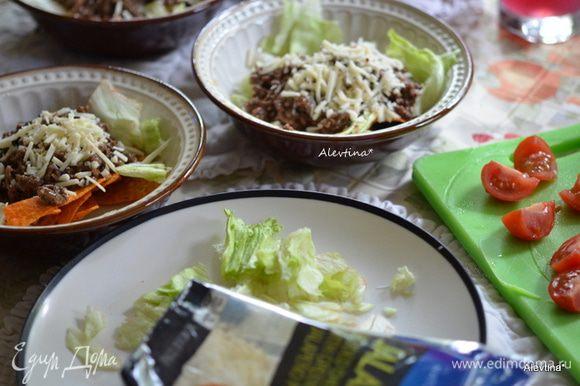 Разложить чипсы кукурузные по тарелкам. Салат нарвать, помидоры разрезать на половинки. Разложить поверх чипсов салат, затем готовый фарш с фасолью, сыр протертый.