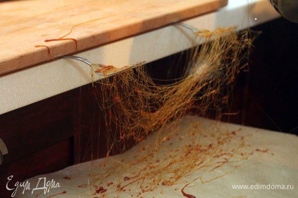 Делаем карамельную нить: Варим сахар, постоянно помешивая, до образования карамели. На поверхность, выложенную пекарской бумагой, разбрызгиваем немного схватившуюся карамель (она должна быть тягучей), горизонтальными движениями, для образования нитей (запутанные нити).