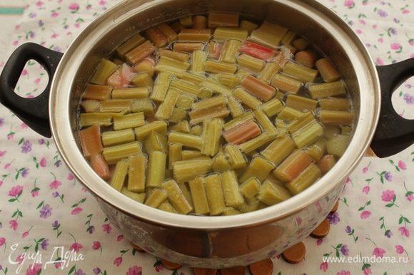 Ревень очистите от жестких волокон, нарежьте мякоть небольшими кусочками. Опустите ревень в кипящую воду с сахаром (количество сахара пробуйте на вкус). Проварите 3-4 мин.