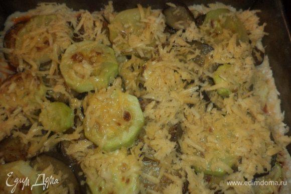 Выложить сверху на соус нарезанные тонкими кольцами помидоры и обжаренные баклажаны и кабачки, посыпать тёртым сыром и орегано. Выпекать при температуре 190 градусов 30 минут.