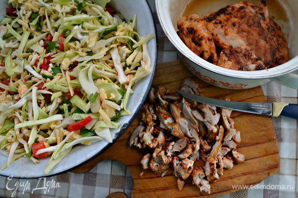 Порезанные овощи, сыр и зелень смешать в миске. Приготовленное куриное филе порезать на кусочки и добавить к овощам.