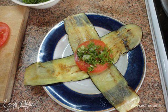 По два язычка из баклажана сложить крестом (обжаренной стороной вверх), на середину положить колечко помидора, затем зелень с чесноком,