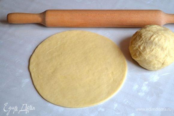 На разделочную поверхность насыпать 1/3 часть стакана сахара. Разровнять рукой. Сверху положить 1/3 часть теста, раскатать в круг.