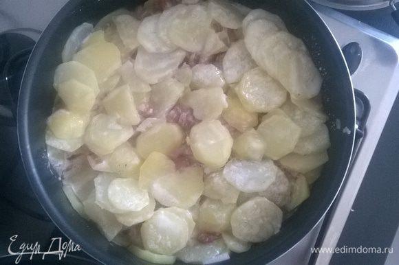 Берем сковороду (у меня Тефаль) или форму для запекания. Выкладываем слоями: половина лука с беконом, сверху половина картофеля, затем снова лук с беконом и наконец покрываем оставшимся картофелем.