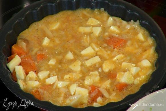 Форму вынуть из духовки, залить тыкву яичной массой, посыпать оставшимся натертым сыром и запекать под грилем еще 5–7 минут.
