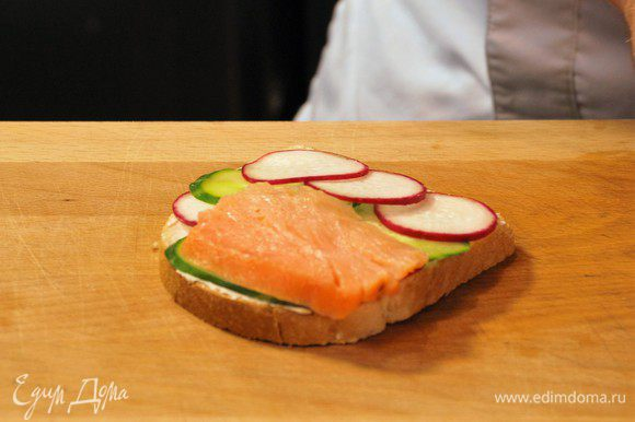 Тонко нарезать лосось и выложить на бутерброд.