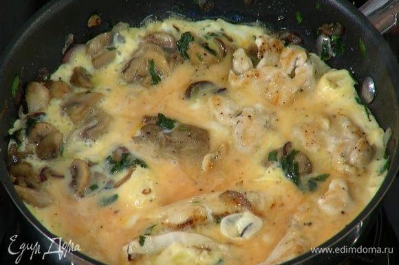 Влить яичную массу в сковороду с курицей и грибами, накрыть крышкой и готовить 3–4 минуты.