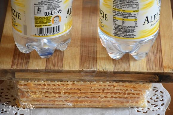 Торт накрыть пищевой пленкой, сверху поставить груз и отправить в холодильник на 2 часа.