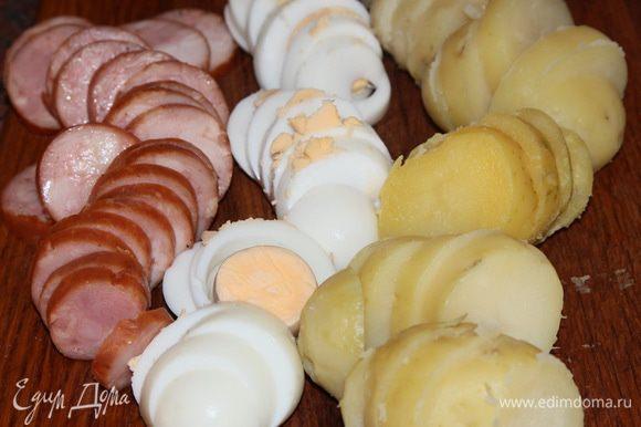 Отвариваем картофель в мундире, яйца вкрутую. Чистим картофель, яйца и колбасу, нарезаем все кольцами толщиной приблизительно 7 мм.