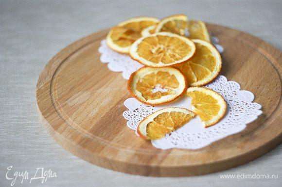Нарезаем тонкими кружочками апельсин. Выкладываем на противень в один слой и ставим сушиться при температуре 100-120 градусов около часа. Если дома влажно, то может уйти больше времени.