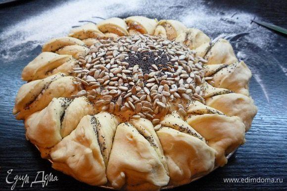 Центр пирога смазываем растопленным сливочным маслом, посыпаем семечками и маком. Смазываем края пирога взбитым яйцом.