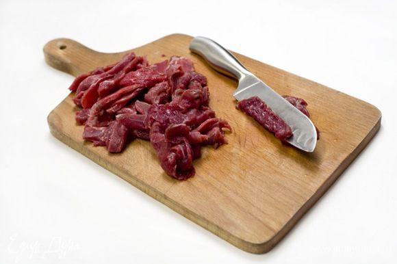 Мясо нарезать на тонкие полоски. Для того, чтобы это было легче сделать, можно предварительно на 30 минут положить его в морозилку.