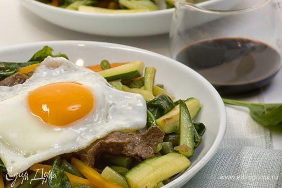 На дно глубокой тарелки выложить рис, в центр поместить обжаренное мясо, по кругу разместить овощи. Полить всё кунжутным маслом и соевым соусом, посыпать перцем чили и кунжутными семечками. Сверху выложить яичницу глазунью. Приятного аппетита!