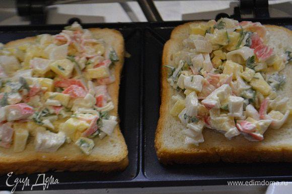 Сэндвичницу разогреть. Уложить хлеб для тостов. Выложить начинку, — не жалеем. И накрыть верхним куском хлеба.
