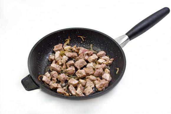 Мелко нарезанный лук обжарить на растительном масле до прозрачности. Добавить кубиками нарезанное мясо и обжарить еще несколько минут.