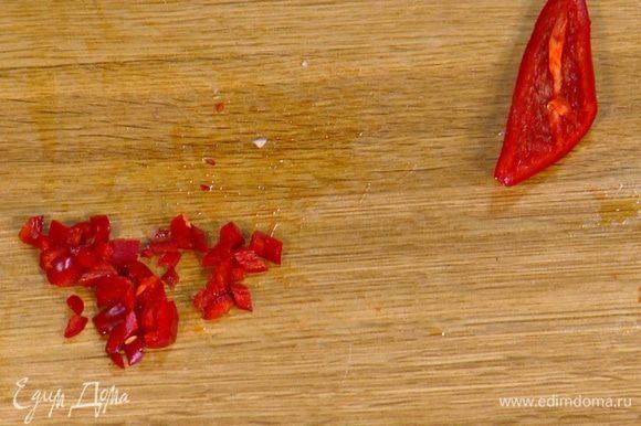 Перец чили, удалив семена, мелко порезать.