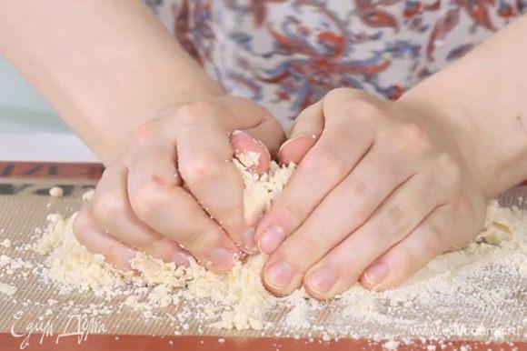 Сначала тесто будет выглядеть как сухая крошка. Его нужно вымешивать руками 5-10 минут до однородности. От теплоты рук тесто станет эластичным и однородным.