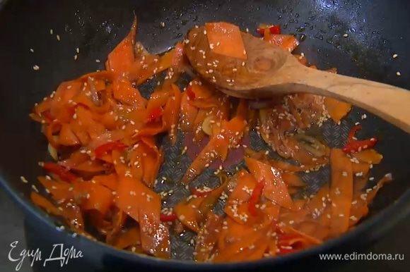 Разогреть в сковороде-вок оливковое и кунжутное масло и обжарить шалот, чеснок и перец чили. Добавить морковь, всыпать кунжут, все перемешать и немного обжарить, затем влить соевый соус, все перемешать и еще немного обжарить. Снять вок с огня, влить оставшийся рыбный соус и еще раз все перемешать.