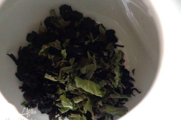 Положить черный чай, сушенные ягоды черной смородины и мяту.