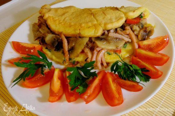 Готовый омлет сложить пополам и выложить на тарелку. Подавать со свежими помидорами.