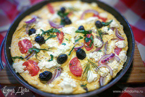 Готовый омлет поперчить, посыпать зеленью и сбрызнуть оливковым маслом.